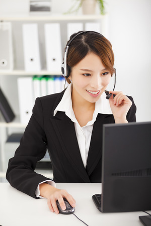telemarketer: young  businesswoman with headset working in office Stock Photo