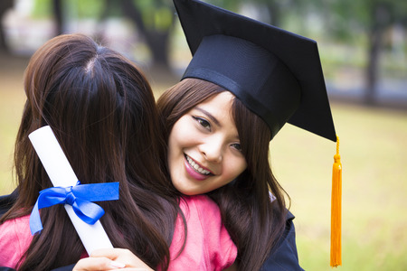 young female graduate hugging her friend at graduation ceremony Banco de Imagens