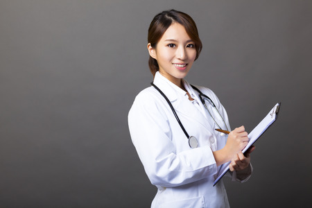healthcare worker: cheerful female doctor with clipboard Stock Photo
