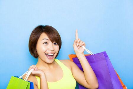 muralla china: Mujer joven con bolsas de compras y apuntando hacia arriba
