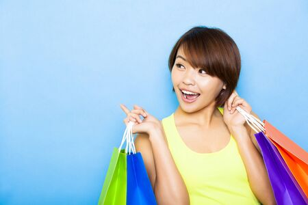 looking to side: young  woman holding shopping bags and looking side