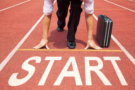 pista de atletismo: hombre de negocios preparándose para la carrera en la pista