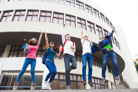 Happy young group of students jumping together photo