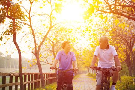 lifestyle: couple de personnes âgées sur le tour de cycle dans le parc