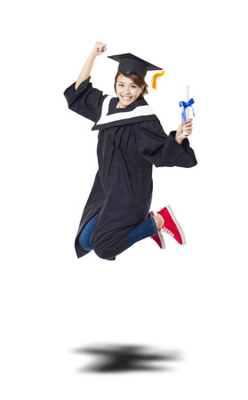 Happy female student in graduate robe jumping against white background Stockfoto