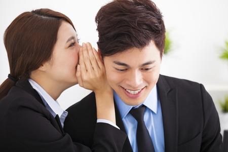 whisper: business gossip between businesswoman and businessman Stock Photo