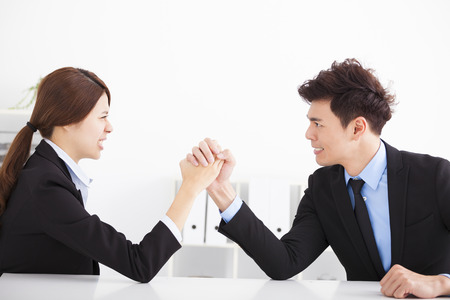 Business man and woman arm wrestling on desk in office