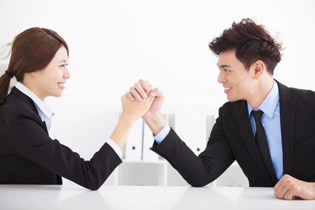 facing: Business man and woman arm wrestling on desk in office