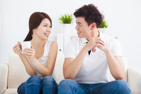 dattes: Jeune couple heureux se d�tendre dans le canap� Banque d'images