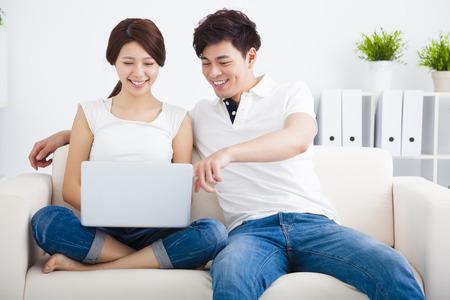 ラップトップ コンピューターとソファの上アジア カップル