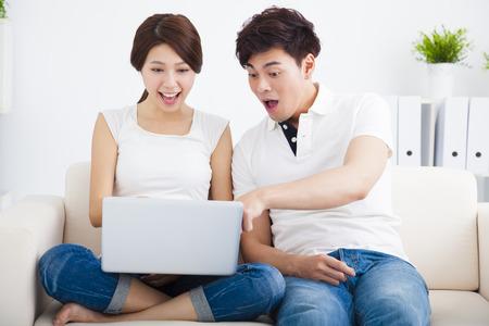 beau jeune homme: Couple surpris sur le canapé avec un ordinateur portable Banque d'images