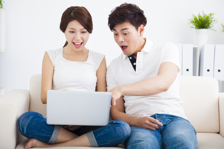 man woman hugging: surprised Couple on sofa with laptop computer