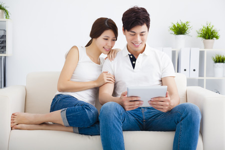 Coppia asiatica sul divano con il computer tablet Archivio Fotografico
