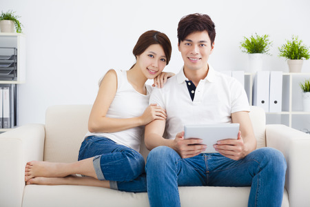 young asian couple: happy young Couple on sofa with tablet