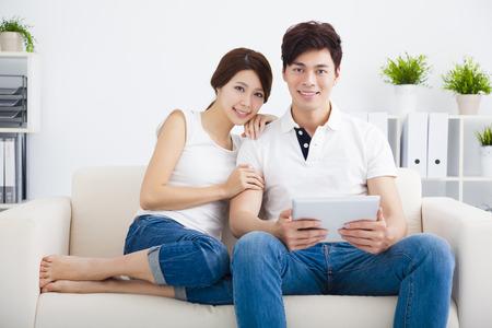 esposas: Pareja joven feliz en el sofá con la tableta Foto de archivo