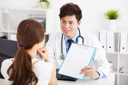 consulta médica: médico hablando con el paciente femenino en la oficina Foto de archivo