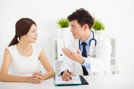 hospital care: asian doctor talking with female patient in  office Stock Photo