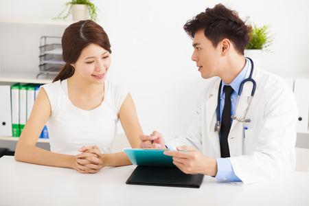 アジアの医者のオフィスで女性患者と話