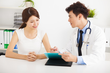 hospital patient: asian doctor talking with female patient in  office Stock Photo