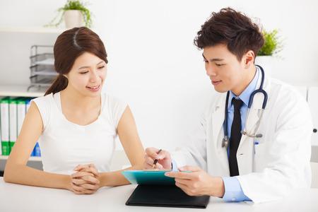 Aziatische arts te praten met vrouwelijke patiënt in het kantoor