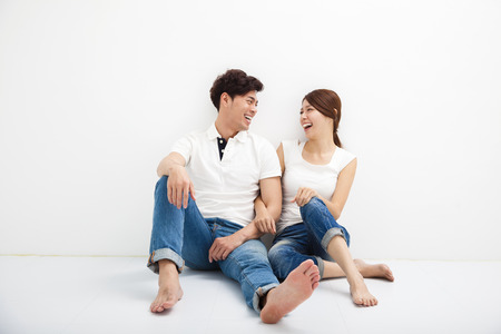 生活方式: 快樂的年輕亞洲夫婦坐在地板上 版權商用圖片