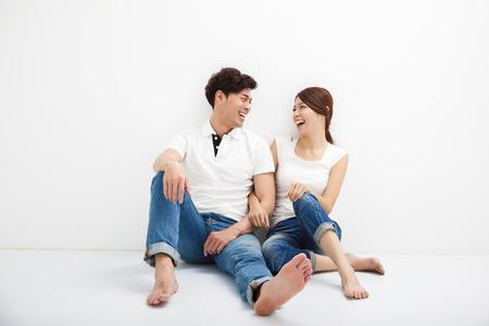 gente sentada: Feliz pareja asiática joven se sienta en suelo