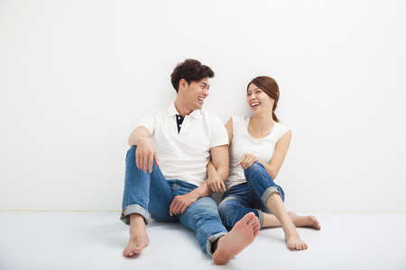 Happy Young asian Couple Sitting On Floor Standard-Bild