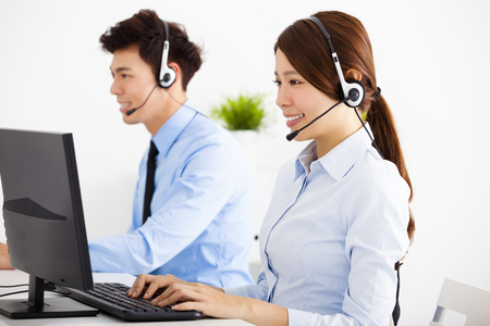 customer services: smiling business man and woman with headset working in office Stock Photo