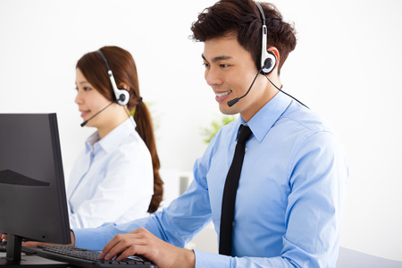 smiling business man and woman with headset working in office Stock Photo