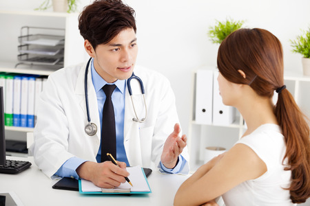 asian medical: doctor talking with female patient in  office