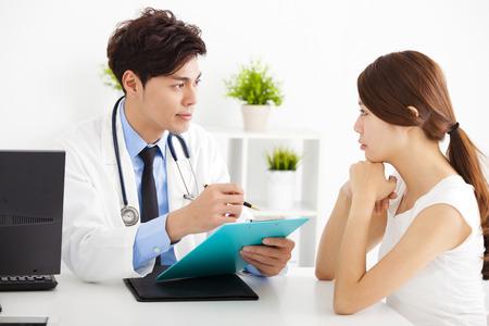 personas escuchando: médico hablando con el paciente femenino en la oficina Foto de archivo