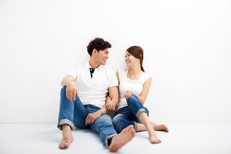 pareja abrazada: Feliz pareja asi�tica joven se sienta en suelo