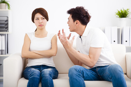 people arguing: Angry young couple sitting on the sofa