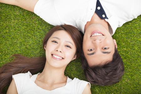 lifestyle: Vista superior de la joven pareja de enamorados que yacen juntos en el césped