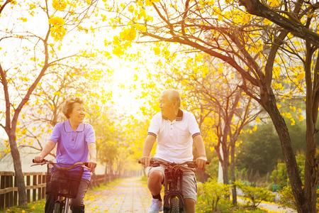 glad äldre par rida på cykel i parken