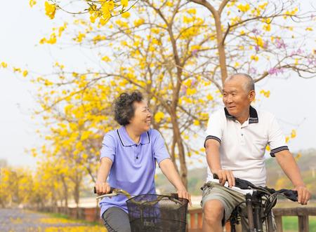 salud y deporte: paseo feliz pareja de ancianos asi�tica en la bicicleta en el parque Foto de archivo