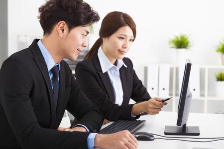 cooperacion: La gente de negocios que tienen reunión y mirando la computadora en la oficina