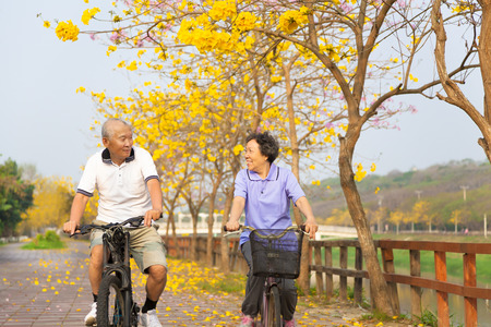 ride: happy asian senior couple ride on bicycle  in the park