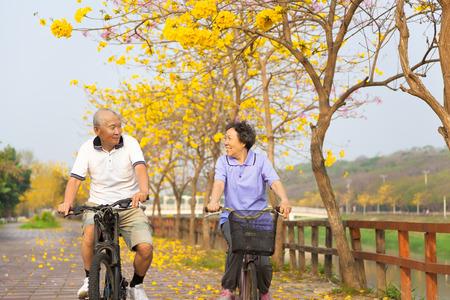 ancianos felices: paseo feliz pareja de ancianos asiática en la bicicleta en el parque Foto de archivo