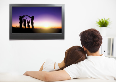 pareja viendo tv: joven pareja viendo la televisi�n concepto espect�culo familiar Foto de archivo