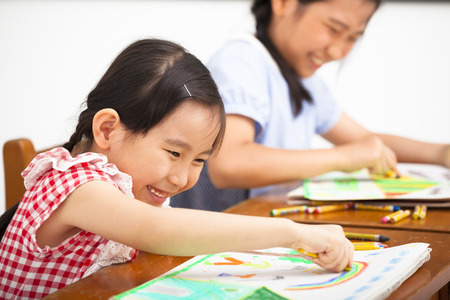 junior education: happy children drawing in the classroom Stock Photo