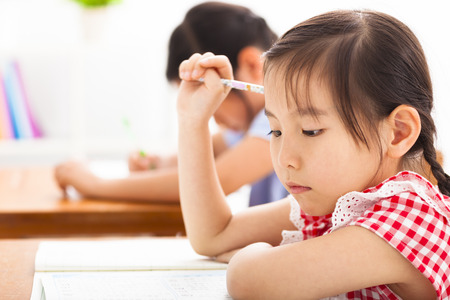 a child: little girl thinking in the classroom