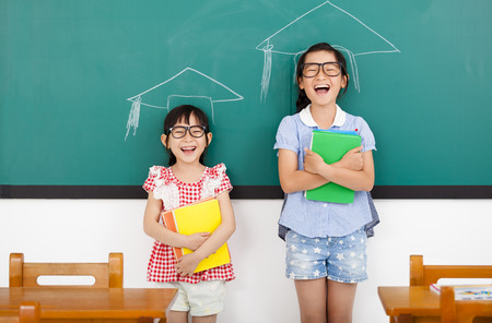 asian child: happy little girls with graduation concept in classroom