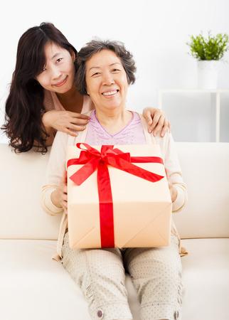 abrazar familia: feliz madre e hija con caja de regalo