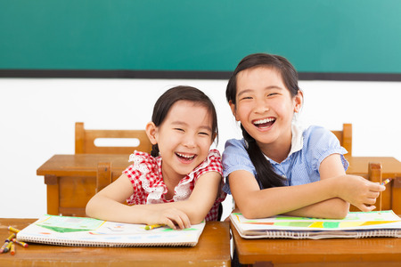 students fun: happy little girls in the classroom