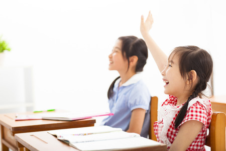happy school children  raised hands in class 版權商用圖片