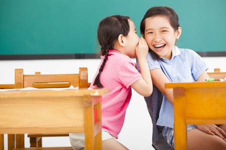 secrets: happy little girls whispering and sharing a secret  in classroom Stock Photo