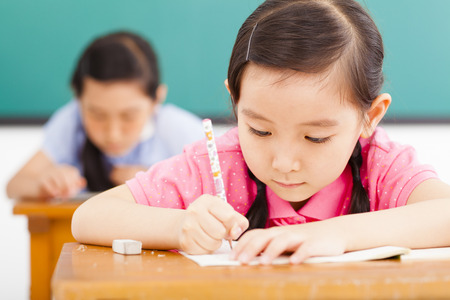 children in classroom with pen in hand