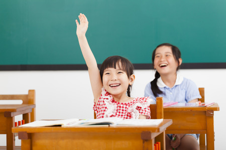 successful student: happy school children  raised hands in class Stock Photo