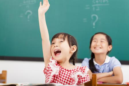 幸せな学校の子供たちは、クラスで手を上げた